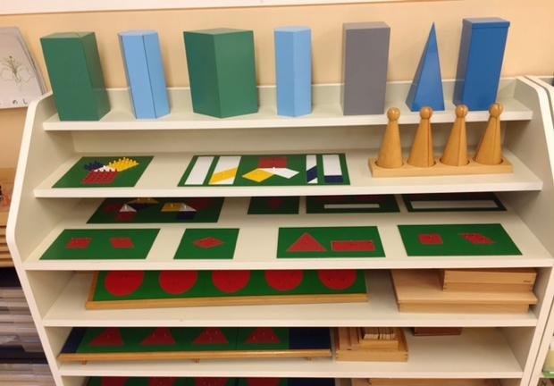小学生向けの上級算数教具が収納してある棚。上段「小学生向け幾何学立体」(Elementary Geometric solids)、「体積」(Metal Volume)。上から2段目「ピタゴラスのはめこみ板」(Theorem of Pythagoras)。