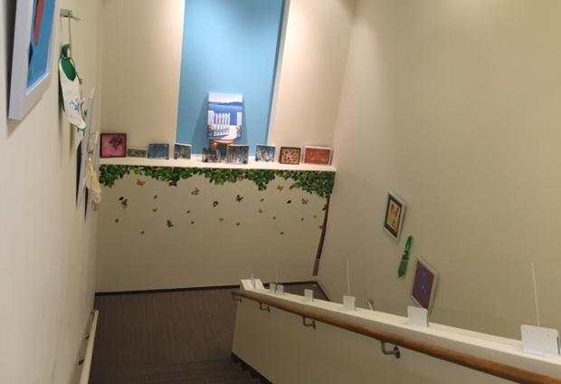階段には、子どもたちのカラフルな作品がずらっと並べられている。