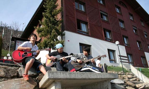 寮を背景に、仲間でギターのセッション。目の前に広がる絶景もすばらしい!